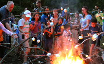 Photo of Campers gathered around a bonfire.